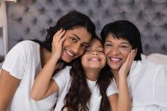 Retrato del abarcamiento multigeneración sonriente en cama Imagen de archivo libre de regalías