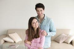 Retrato del abarcamiento sonriente de los pares jovenes en casa, relati feliz Fotografía de archivo