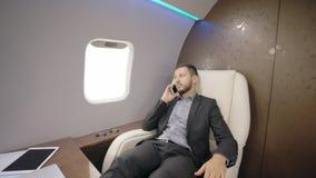 Retrato del abogado joven del hombre de negocios que habla en el teléfono en jet privado de lujo metrajes