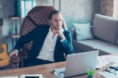 Retrato del abogado rico atractivo que se sienta en su escritorio en el trabajo s imagenes de archivo