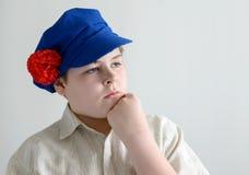 Retrato del adolescente aboy en el casquillo nacional ruso con los clavos Imágenes de archivo libres de regalías