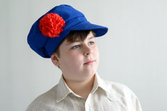 Retrato del adolescente aboy en el casquillo nacional ruso con los clavos Imagenes de archivo