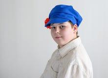 Retrato del adolescente aboy en el casquillo nacional ruso con los clavos Foto de archivo libre de regalías