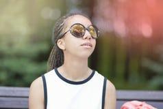 Retrato del adolescente afroamericano con los Dreadlocks largos que presentan en parque al aire libre en gafas de sol Fotos de archivo
