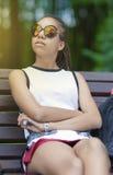 Retrato del adolescente afroamericano con los Dreadlocks largos que presentan en parque al aire libre en gafas de sol Foto de archivo libre de regalías