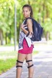 Retrato del adolescente afroamericano positivo Presentación con los protectores de la mochila y de la rodilla al aire libre en pa Imagenes de archivo