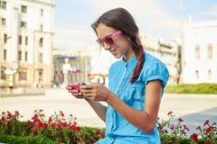 Retrato del adolescente bonito que mira algo en su smartp Foto de archivo libre de regalías