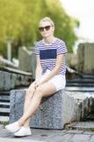 Retrato del adolescente caucásico relajante que presenta en parque verde del verano Imágenes de archivo libres de regalías