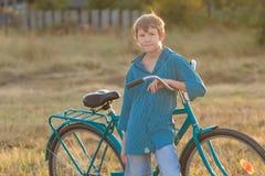 Retrato del adolescente con la bici azul en campo de granja Foto de archivo libre de regalías