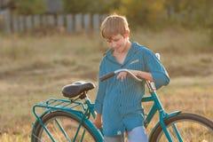 Retrato del adolescente con la bici retra en campo de granja Foto de archivo libre de regalías