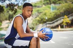 Retrato del adolescente con la bola que se sienta en banco Foto de archivo libre de regalías