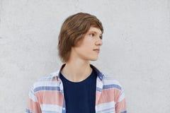 Retrato del adolescente con la camiseta que lleva y la camisa del peinado de moda que miran lejos que tienen pensamientos profund Imagen de archivo