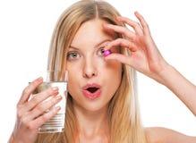 Retrato del adolescente con la taza de agua que muestra la píldora Fotos de archivo libres de regalías