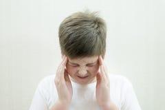 Retrato del adolescente con un dolor de cabeza Imagenes de archivo