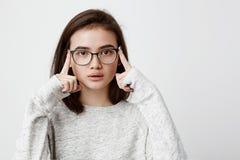 Retrato del adolescente concentrado con las lentes que llevan oscuras del pelo recto que miran pensativamente la custodia de la c Fotos de archivo libres de regalías