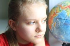 Retrato del adolescente de la chica joven en casa que mira con el globo Foto de archivo