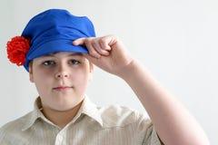 Retrato del adolescente del muchacho en el casquillo nacional ruso con los clavos Imágenes de archivo libres de regalías