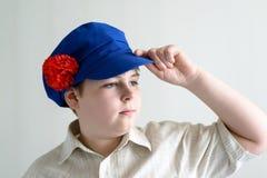 Retrato del adolescente del muchacho en el casquillo nacional ruso con los clavos Fotos de archivo libres de regalías