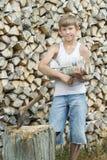 Retrato del adolescente en el fondo de la pila de la leña Foto de archivo libre de regalías