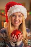 Retrato del adolescente en el sombrero de santa que sostiene la bola de la Navidad Imagen de archivo libre de regalías