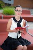 Retrato del adolescente en el uniforme escolar que se sienta en banco con Imagen de archivo