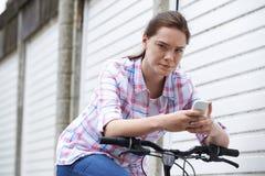 Retrato del adolescente en la bici que manda un SMS usando el teléfono móvil Foto de archivo