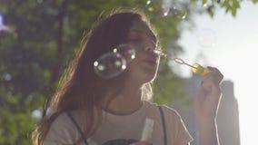Retrato del adolescente en las burbujas de jabón del parque que soplan en la cámara Tiempo lindo del gasto de la mujer joven sola metrajes