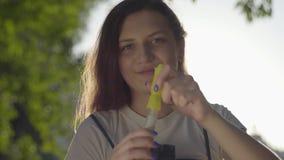 Retrato del adolescente en las burbujas de jabón del parque que soplan en la cámara Tiempo lindo del gasto de la mujer joven sola almacen de video