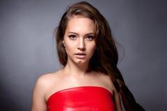 Retrato del adolescente en un vestido rojo en un fondo gris Imagenes de archivo