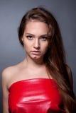 Retrato del adolescente en un vestido rojo en un fondo gris Imagen de archivo libre de regalías