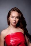 Retrato del adolescente en un vestido rojo en un fondo gris Fotos de archivo
