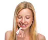 Retrato del adolescente feliz que aplica el lápiz labial higiénico Fotos de archivo