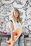 Retrato del adolescente feliz que sostiene el monopatín en casa Foto de archivo libre de regalías