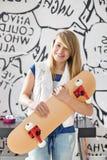 Retrato del adolescente feliz que sostiene el monopatín en casa Fotografía de archivo libre de regalías