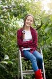 Retrato del adolescente feliz sonriente que se sienta encima de la escalera de mano en el jardín Fotografía de archivo