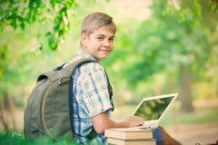 Retrato del adolescente hermoso con el ordenador portátil y los libros en el wonde Fotografía de archivo
