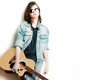 Retrato del adolescente hermoso en el fondo blanco que sostiene su guitarra Foto de archivo libre de regalías