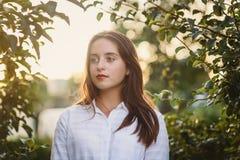 Retrato del adolescente hermoso en la blusa blanca en el manzanar en verano Imagen de archivo