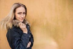 Retrato del adolescente hermoso en la chaqueta que se opone a la pared Imagenes de archivo