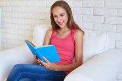 Retrato del adolescente hermoso que lee un libro en acogedor blanco Fotografía de archivo