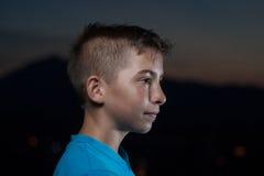 Retrato del adolescente joven en un paisaje de la montaña en el tiempo crepuscular Imagen de archivo