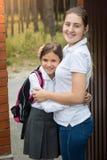 Retrato del adolescente lindo en el uniforme escolar que abraza a su madre Imagen de archivo