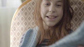 Retrato del adolescente lindo positivo que saca la bufanda azul caliente de su cuello y que la lanza para arriba, sonriendo almacen de metraje de vídeo