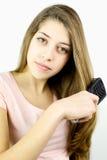 Retrato del adolescente lindo que cepilla el pelo rubio largo Foto de archivo libre de regalías