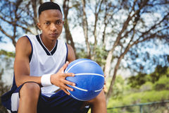 Retrato del adolescente masculino con la bola que se sienta en banco Fotos de archivo libres de regalías