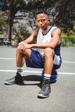 Retrato del adolescente masculino que se sienta en baloncesto Foto de archivo