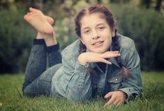 Retrato del adolescente mientras que miente en parque del verde del verano Imagen de archivo libre de regalías