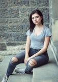 Retrato del adolescente moreno joven hermoso caucásico blanco de la muchacha con los ojos verdes azules en vaqueros rasgados, cam Imagen de archivo libre de regalías