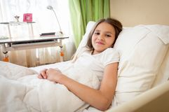 Retrato del adolescente moreno sonriente que miente en dormitorio Foto de archivo