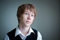 Retrato del adolescente pensativo en fondo gris. Fotos de archivo